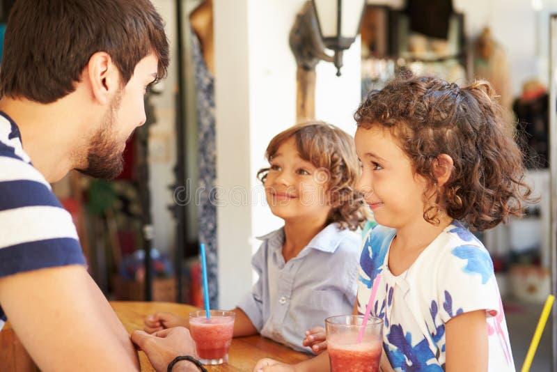 喝果子圆滑的人的孩子在餐馆 库存照片