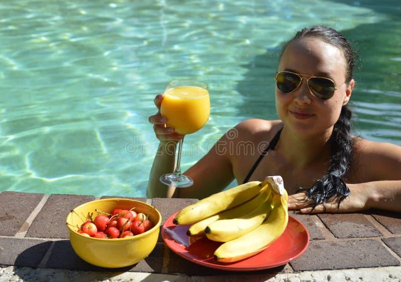 喝橙汁和吃在水池的女孩果子 免版税库存照片