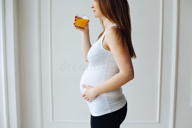 喝橙汁瓶的孕妇在训练以后 有玻璃的年轻人孕妇用被隔绝的汁液  库存照片