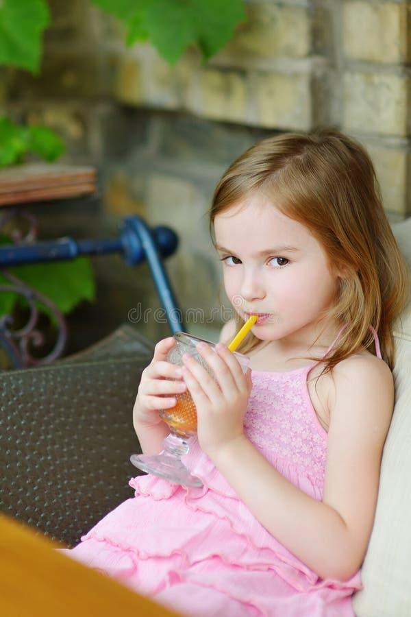 喝橙汁的可爱的小女孩 库存图片
