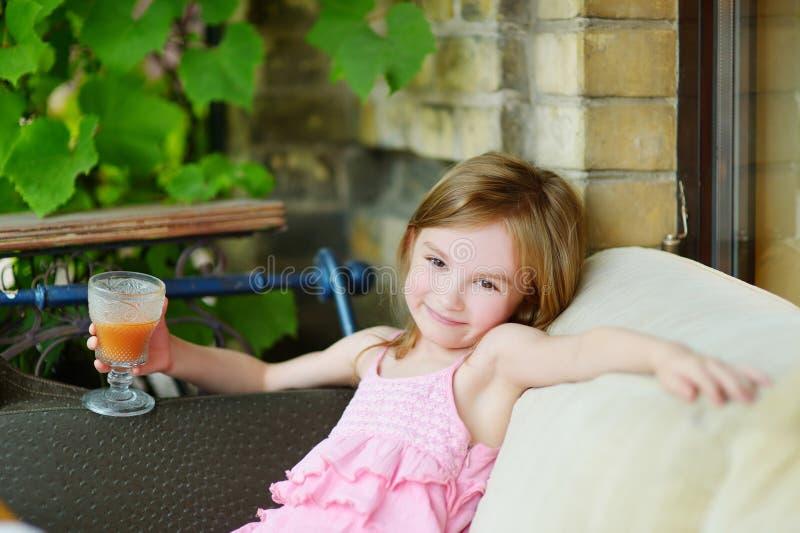 喝橙汁的可爱的小女孩 免版税库存照片