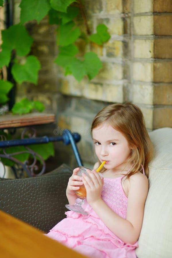 喝橙汁的可爱的小女孩 库存照片