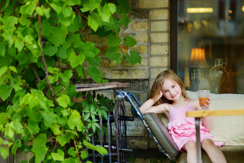 喝橙汁的可爱的小女孩 免版税库存图片
