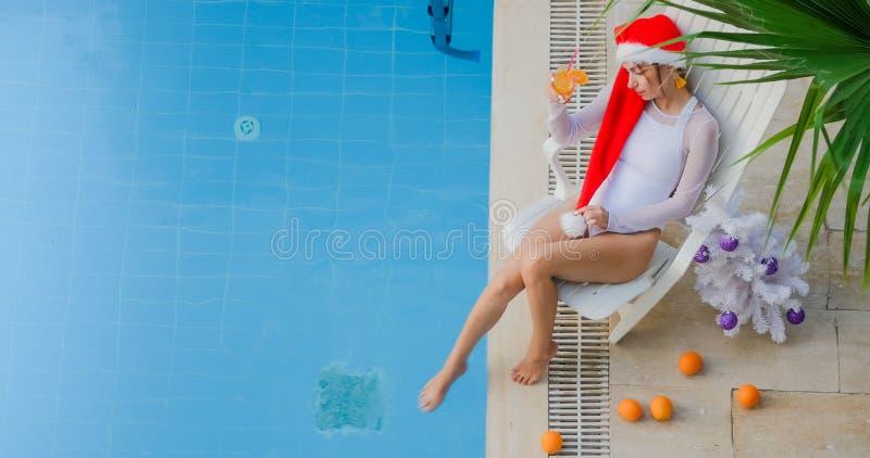 喝橙汁的圣诞节妇女 库存图片