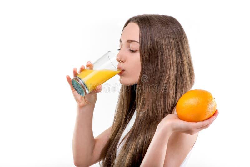 喝橙汁的女孩 免版税图库摄影