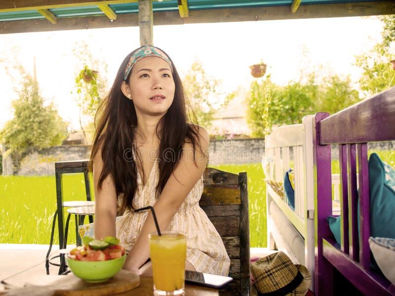 喝橙汁的年轻美丽和愉快的亚裔中国妇女吃健康沙拉在有机食品咖啡店户外enjo 库存照片