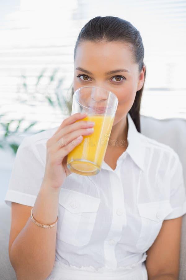 喝橙汁的快乐的俏丽的妇女坐舒适couc 图库摄影