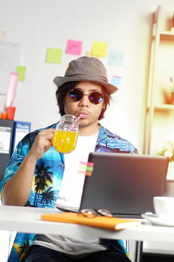 喝橙汁的时髦的年轻人,当研究夏天时 库存图片