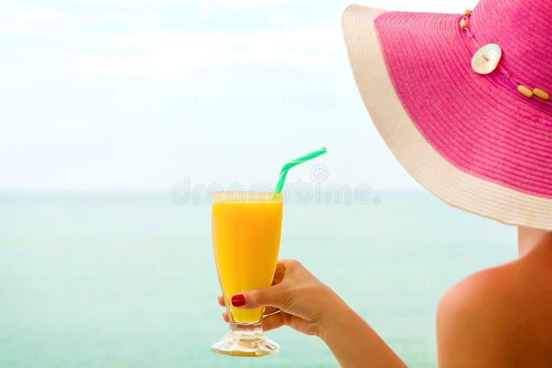 喝橙汁,在海滩的妇女 免版税库存图片