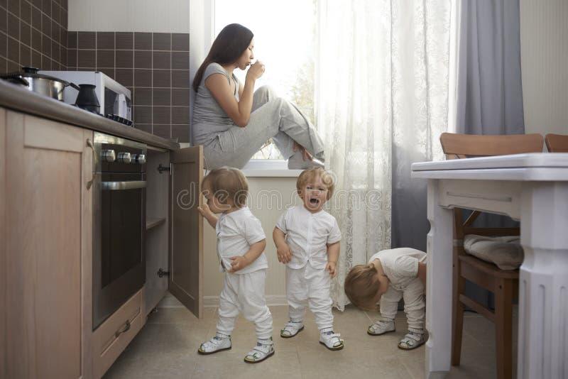 喝母亲的咖啡的唯一的安全的地方有许多孩子的 免版税库存照片
