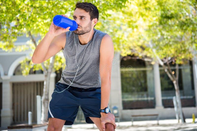 喝淡水的英俊的赛跑者 免版税库存照片