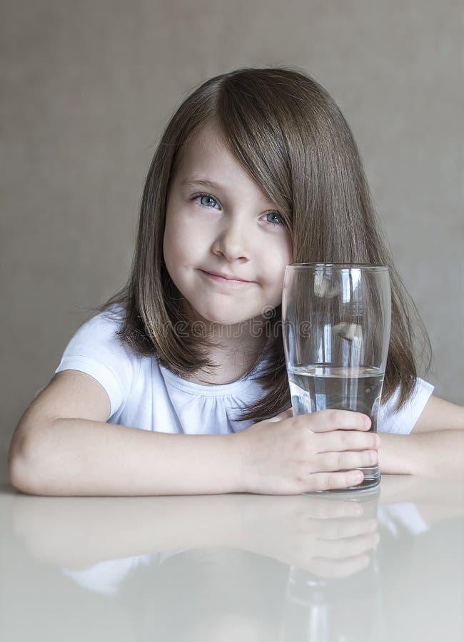 喝清楚的水的愉快的美丽的小女孩 拿着透明玻璃的微笑的婴孩画象 免版税库存图片