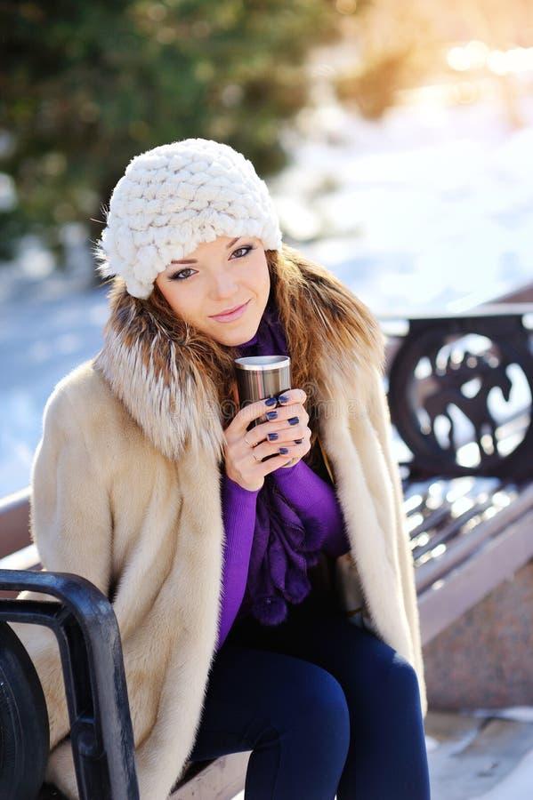 喝温暖的饮料的冬天女孩 免版税库存图片