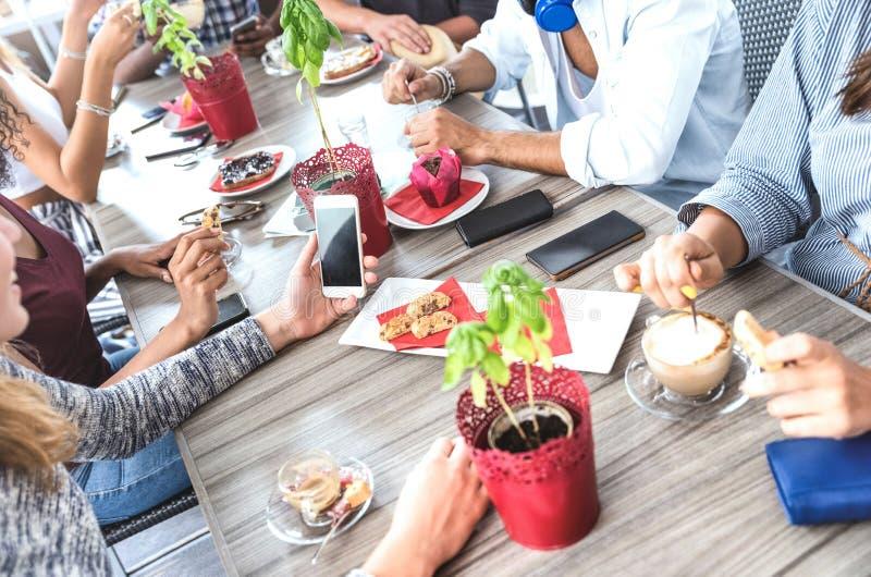 喝热奶咖啡的顶端观点的朋友在咖啡馆餐馆-获得的人们一起吃和使用手机的乐趣 库存图片