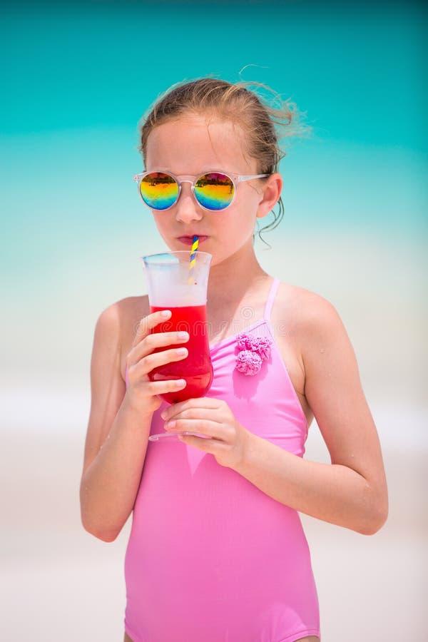 喝热带汁液的小女孩在海滩 免版税库存照片