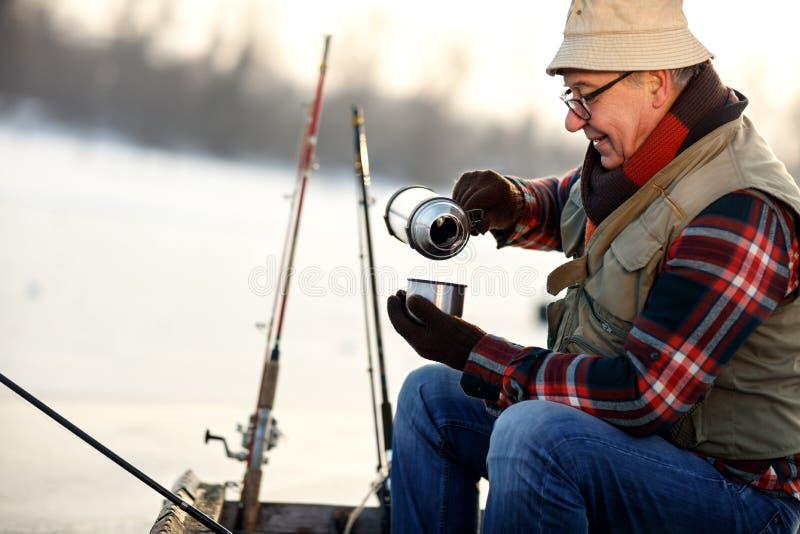喝热的发球区域的渔夫,当钓鱼从小船时 免版税库存照片