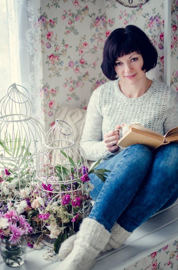 喝热的茶和读书的美丽的妇女 库存照片