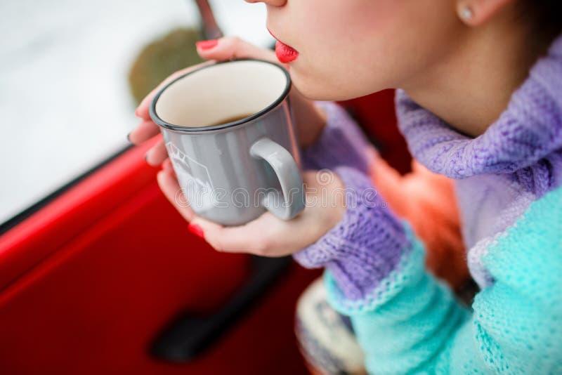 喝热的茶特写镜头的年轻女人 获得温暖 免版税库存照片