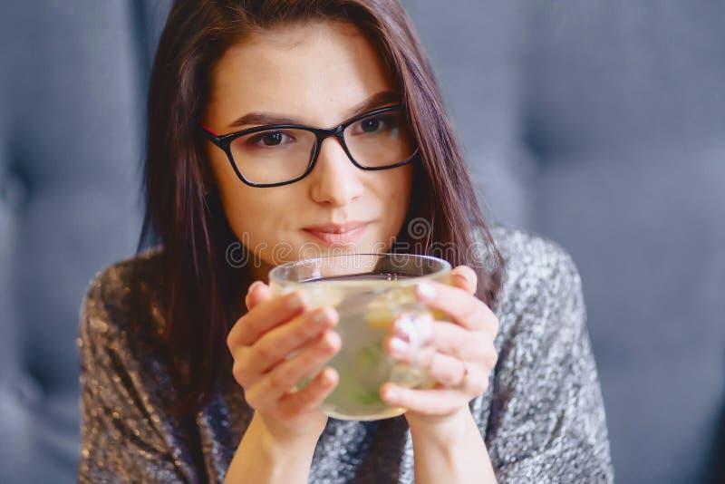 喝热的茶用柠檬的一个年轻俏丽的女孩的画象 库存照片