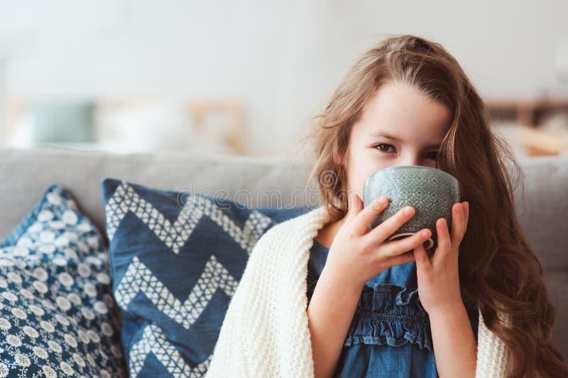 喝热的茶的儿童女孩从流感恢复 库存图片