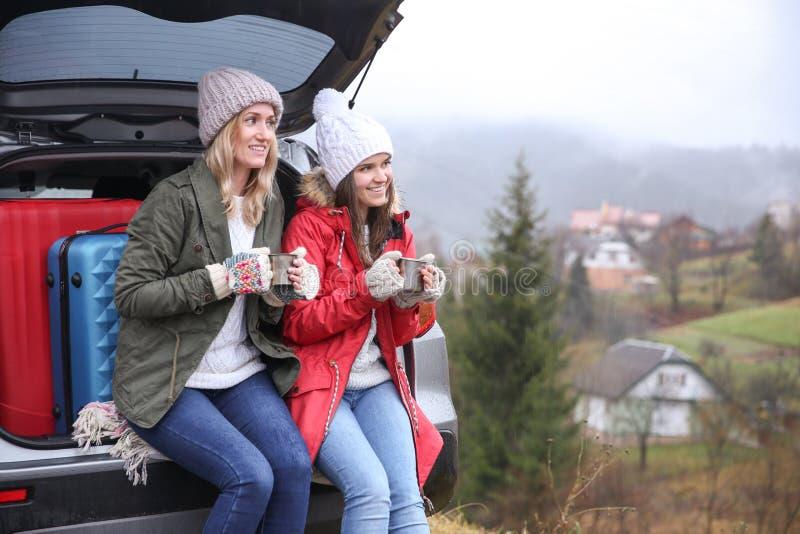 喝热的茶的女性游人在汽车附近 免版税库存照片