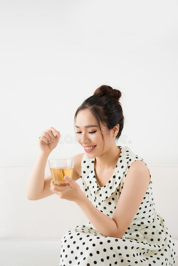 喝热的茶的年轻可爱的亚裔妇女 免版税库存图片