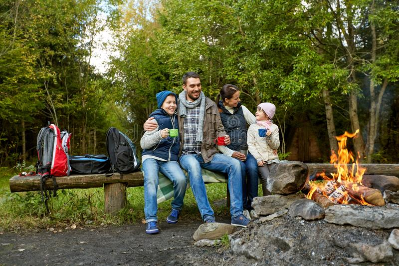 喝热的茶的愉快的家庭在阵营火附近 库存照片