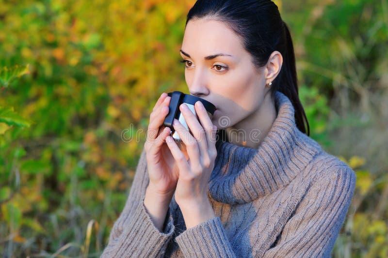喝热的茶的美丽的妇女户外 免版税库存照片