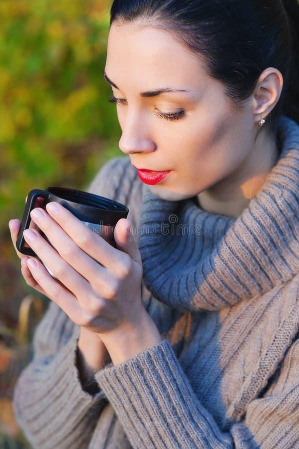 喝热的茶的美丽的妇女户外 库存照片