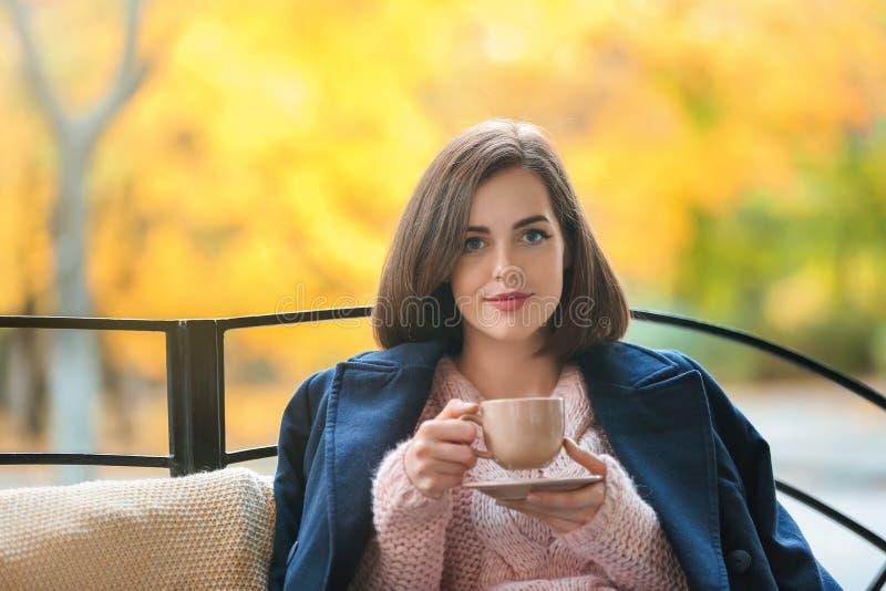 喝热的茶的美丽的年轻女人户外 库存图片