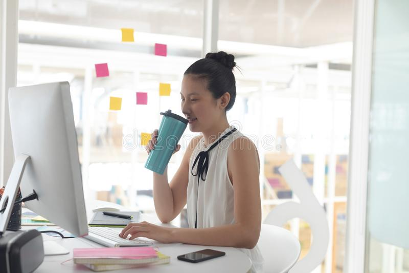 喝热的饮料的女性图表设计师,当研究计算机在书桌时 免版税库存照片