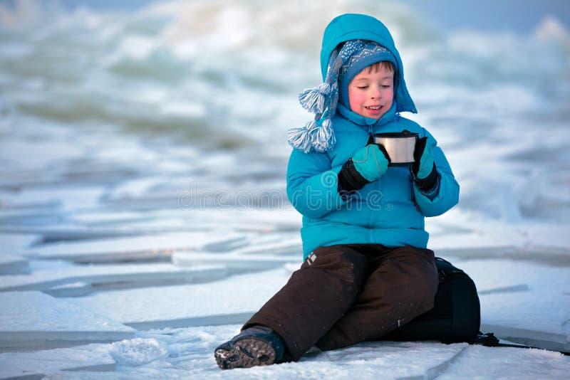 喝热茶的逗人喜爱的小男孩在冬天 免版税图库摄影