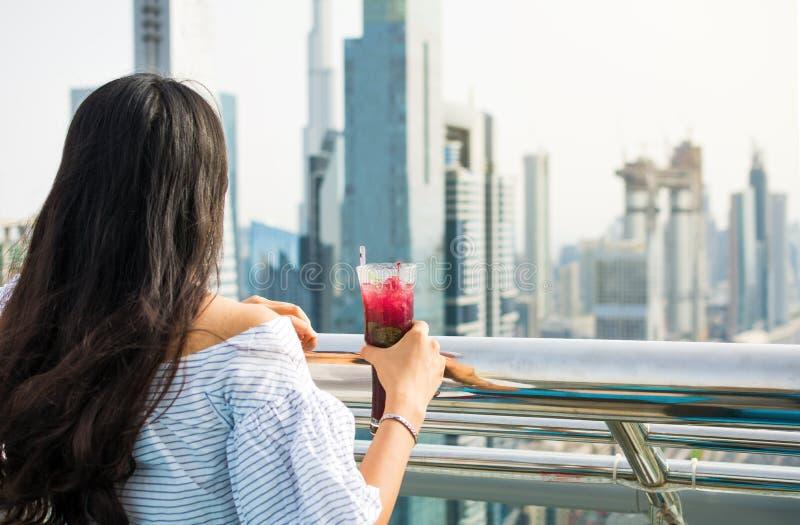 喝的女孩一杯有迪拜视图 库存图片