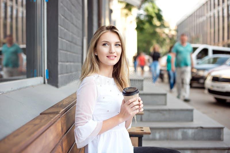 喝的美女走在城市和由一个室外咖啡馆拿走咖啡 城市早晨场面 免版税图库摄影