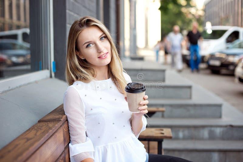 喝的美女走在城市和由一个室外咖啡馆拿走咖啡 城市早晨场面 免版税库存图片