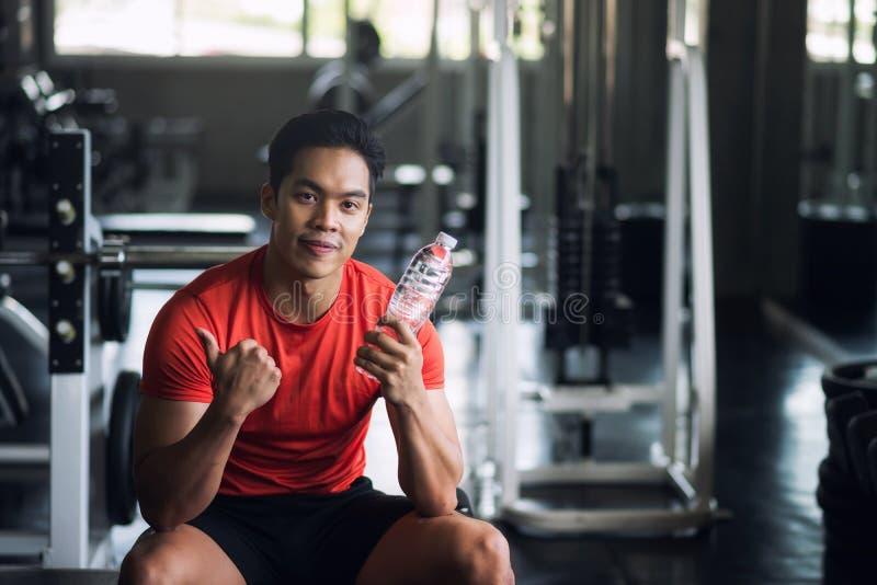 喝的肌肉人举行水在健身房 库存照片
