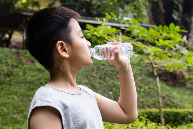 喝矿泉水的亚裔中国小男孩 库存图片