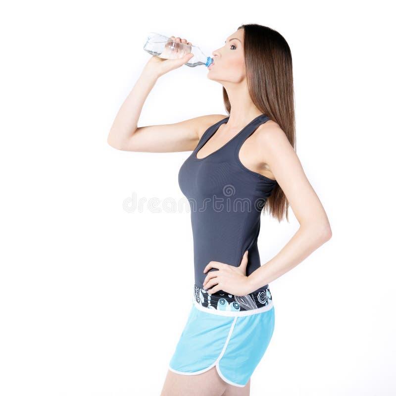 喝矿泉水的美丽的妇女 免版税库存照片