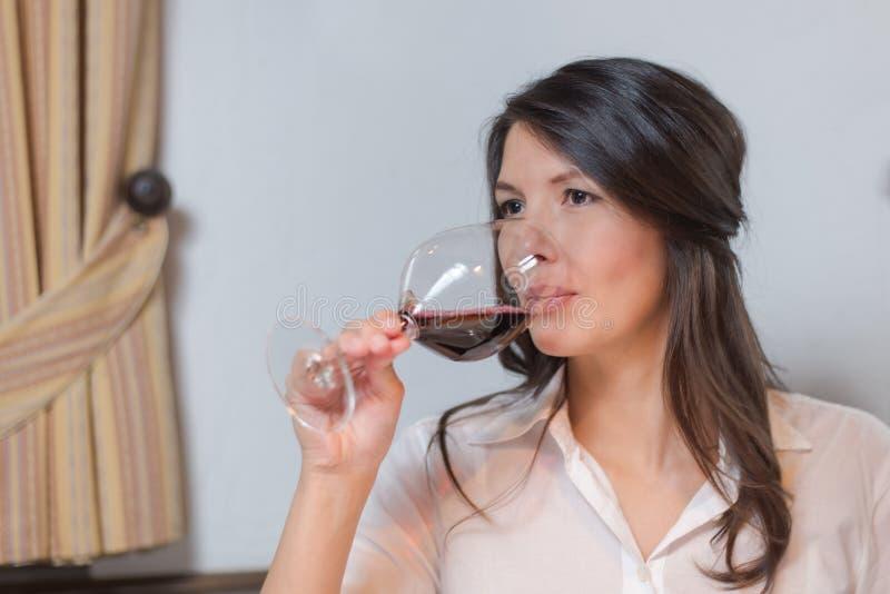 喝红葡萄酒的可爱的妇女 库存照片