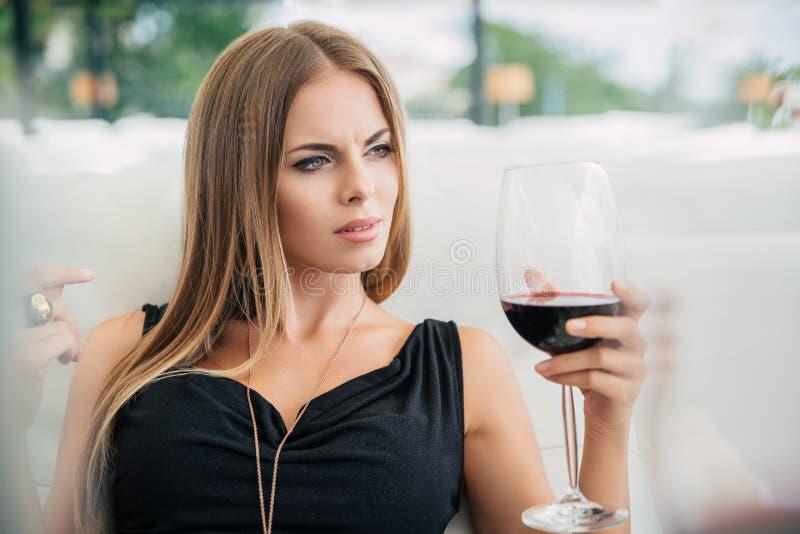 喝红葡萄酒的妇女在餐馆 免版税图库摄影