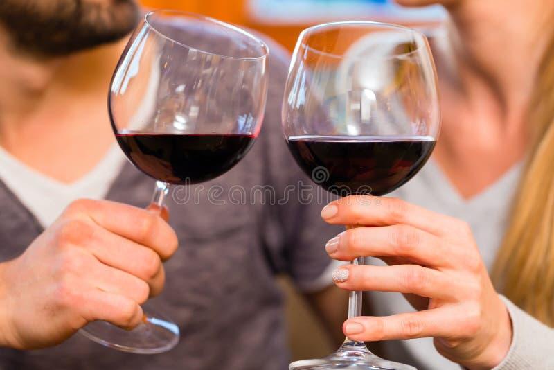 喝红葡萄酒的年轻英俊的夫妇 免版税库存图片