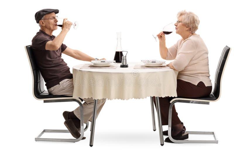 喝红葡萄酒的年长夫妇在日期 免版税库存照片