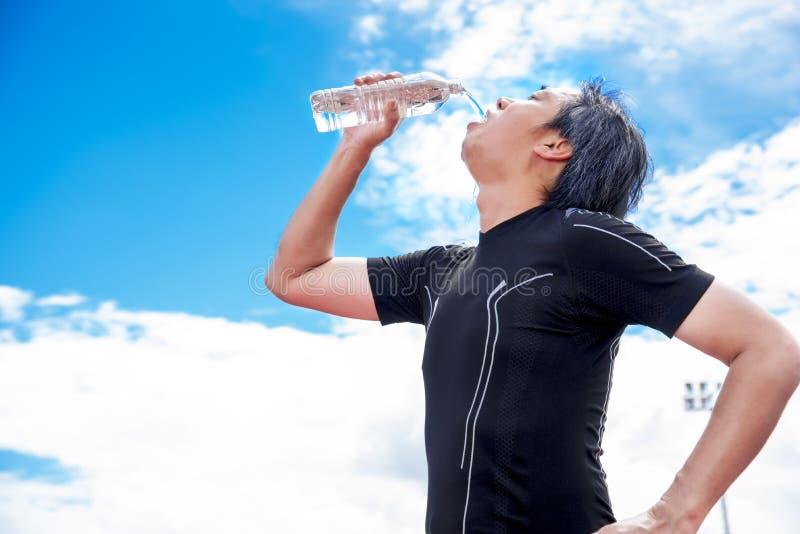 喝纯净的水的运动员,当作为断裂或休息时间,放松和体育概念 免版税库存图片