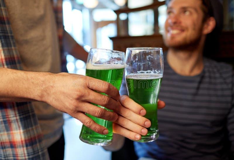 喝绿色啤酒的男性朋友在酒吧或客栈 免版税库存照片