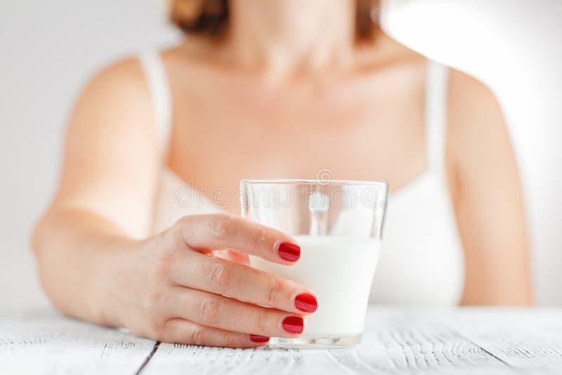 喝美丽的照相机享用玻璃愉快的查找的牛奶微笑的妇女年轻人 免版税库存照片