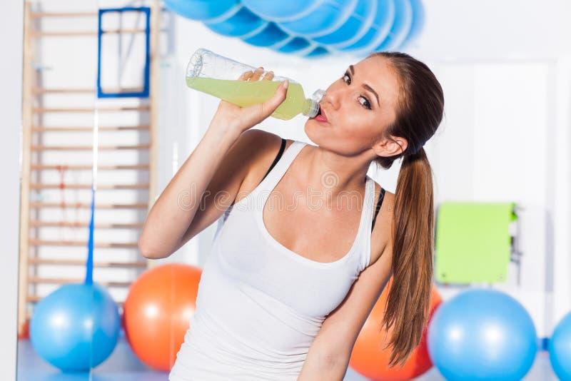 喝能量饮料,健身房的女孩 她情感愉快和有很多 免版税图库摄影