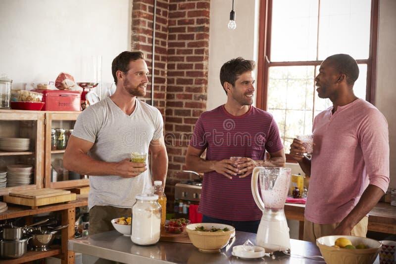 喝自创圆滑的人的三个男性朋友在厨房里 免版税库存图片