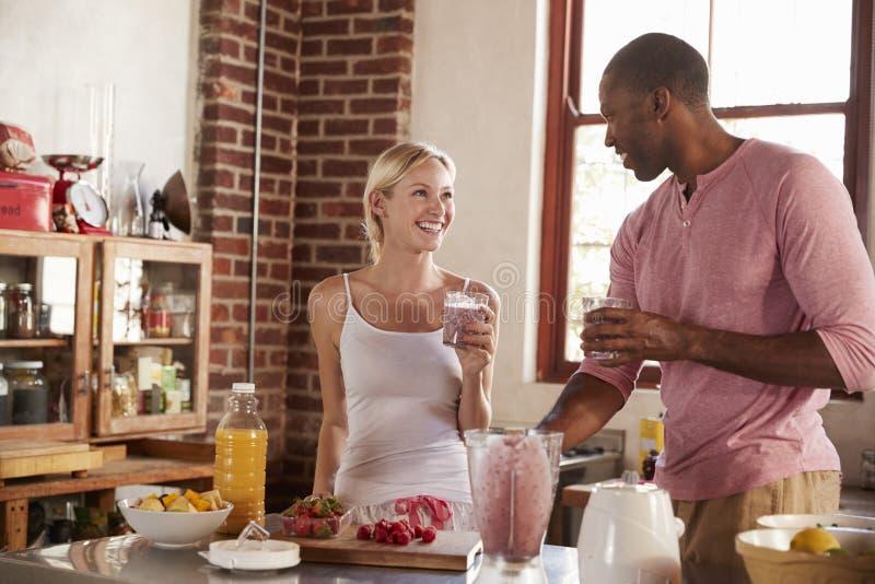 喝自创圆滑的人的混合的族种夫妇在厨房里 免版税库存图片