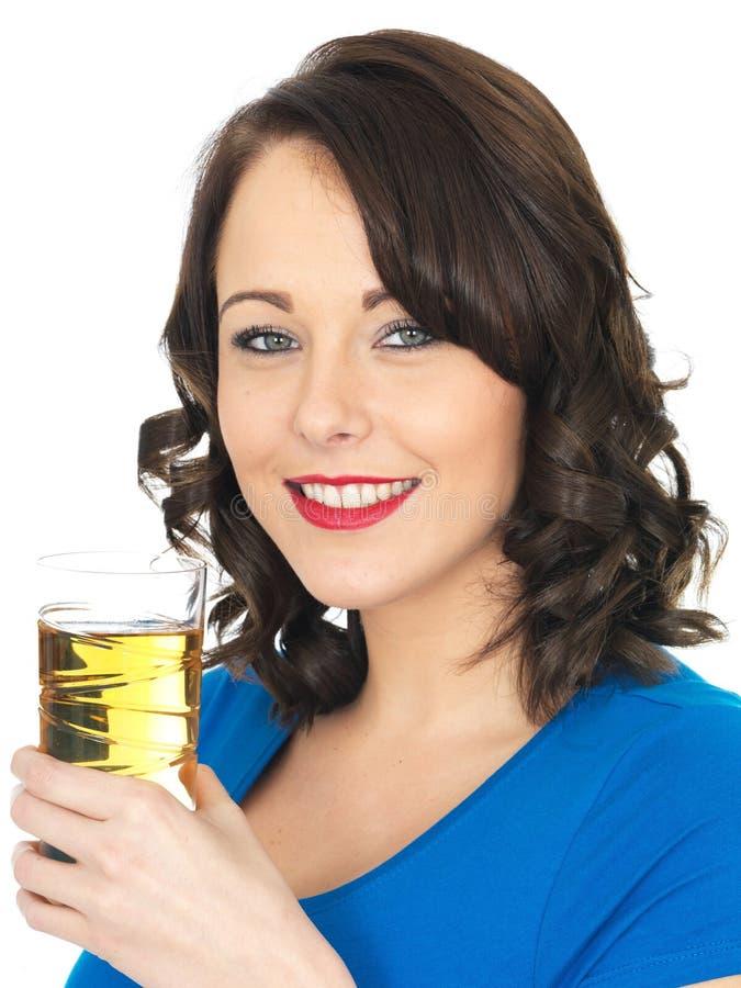 喝苹果汁的可爱的少妇 免版税库存图片