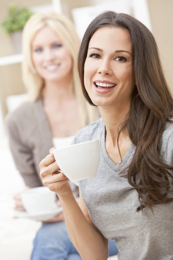 喝茶或咖啡的愉快的妇女朋友 免版税库存照片